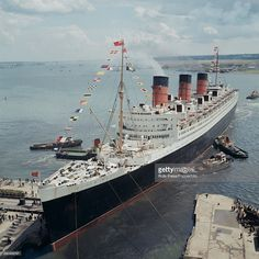 View of Cunard ocean liner RMS Queen Mary being assisted by various tug boats as she arrives in port at Southampton following a transatlantic crossing to England in 1965.