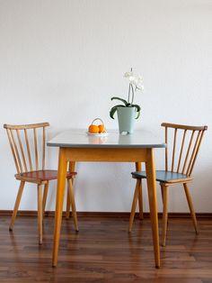 Der Küchentisch mit kleiner Schublade stammt aus den 50er, 60er Jahren. Er hat eine Resopal Oberfläche und die Beine sind aus Holz. Die passenden S...