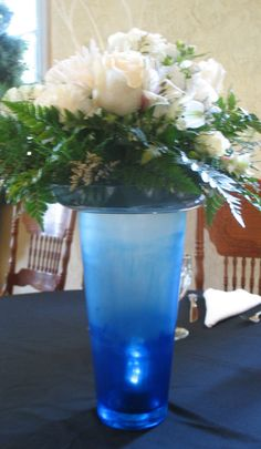 Centerpiece with white midollino sticks, tree fern, leather, Vendela roses, white stock, white spray roses, white alstromeria, antique white wax, white carnations, Fuji spider mum, and misty arranged atop a hand painted sea glass blue ombré vase with light inside. Sea Glass, Glass Vase, Burlap Centerpieces, White Spray Roses, Spider Mums, Vase With Lights, White Carnation, Tree Fern