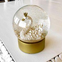 En elegant svan-snöglob med gyllene detaljer! Skaka och se hur guldglitter yr runt svanen i sin snökula. Perfekt som present till namngivning, dop och babyshower!