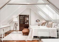 chambre adulte mansardée avec un grand lit et ottoman couleur marron