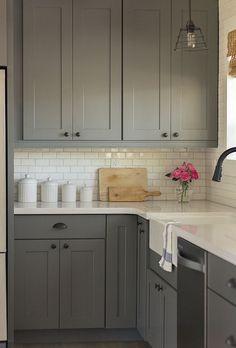 downstairs kitchen: gray kitchen cabinets, white subway tile backsplash, silestone blanco white quartz counters, apron front sink. by MM87