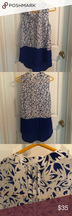 """Anthropologie sleeveless tunic Maeve in blue print EUC cobalt blue 100% silk blouse from Maeve, sold at Anthropologie. The top 2/3 of the tunic is a hidden placket/button front & the material is printed with an abstract print in white and blue. The bottom 1/3 is a high-low hemline solid silk cobalt. Can be worn with cigarette pant and flats, a belt, heels and a skirt or boyfriend jeans and chucks. Very versatile. Measurements- length in ft- 27"""", length in back 32"""". 18"""" bust, 9"""" arm opening…"""