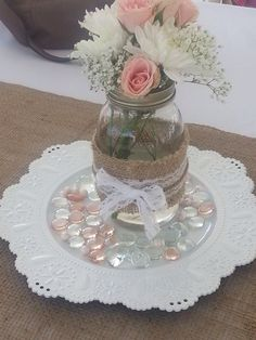 Center pieces for bridal shower, lace chargers found at michaels, with a burlap runner, mason jar wrapped in burlap and lace with white and pink flowers, and gems scattered Bridal Shower Centerpieces, Bridal Shower Favors, Baby Shower Decorations, Flower Decorations, Mason Jar Centerpieces, Wedding Decorations, Girl Baptism Decorations, Burlap Decorations, Burlap Centerpieces