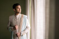 A cream sherwani with gold embroidered motifs and a turquoise dupatta for Groom Bhavesh's wedding