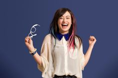 Stock Photo : Portrait of young woman with dyed hair holding glasses