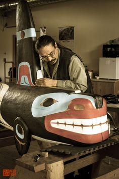 Artist Keith Wolf carving an Orca totem