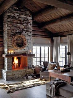 49 heart-warming fireplaces in warm and cozy living spaces, just like this rustic log cabin chalet with floor to ceiling stone chimney and fireplace, wooden mantle, vintage solid wood furniture, gray scroll arm accent chair, cowhide pillows and rugs, and a charming DIY branch wreath on the hearth.