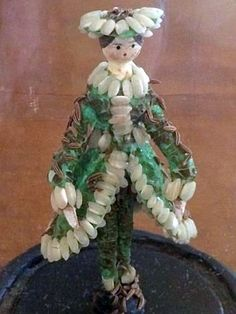Old Wooden Peg Doll dressed in Sea Shell Clothes