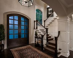 Beautiful Entry - colors, oversized door, wainscoting, turning stairs, hardwood, and window!