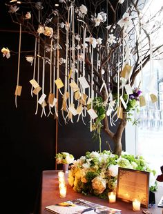 Escort card table, we placed a six-and-a-half foot tree decorated with white Cymbidium orchids at the middle of the table and the escort cards were hung from the branches by ivory satin ribbon.