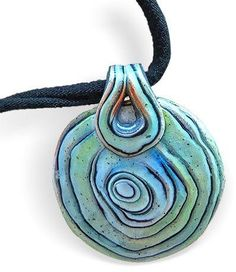 his pendant by Patricia Roberts-Thompson is the result of her playing with Samantha Burroughs' Oyster Watercolor tutorial. Its loose circles and watery colors make your eyes dive right in. Patricia added distressing powders to her color combinations and enlarged the design adding a bail fabricated from the same batch. Samantha admits that she developed her clever tutorial by studying Maggie Maggio's Watercolor Torn Paper instructions from some years back. No criticism here! I enjoy the…