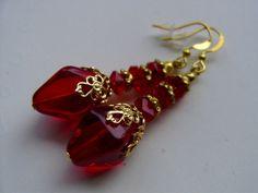 Die Sonne und auch Kerzenlicht bringt hier das Funkeln in diese feurigen Doppelpyramiden in goldige Ornamente gefasst als Ohrringe in leuchtendem rot!