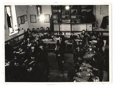 Yeshiva bokhrim, eat and read around tables in a Yeshiva. Slovakia, 1920s.