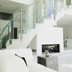 Kaareva portaikko ja takka yhdistyvät näyttäväksi kokonaisuudeksi olohuoneessa
