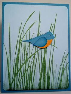 """The grass from the Inspired by Nature stamp set has a perfect """"bent blade"""" to use as abird or bug perch. I created a simple bluebird using the Bird Builder Punchand Marina Mist cardstock.The breast is a piece of toren More Mustard cardstock"""