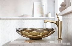 The minimal Margaux faucet in Vibrant French Gold and the richly ornate Briolette sink - a brilliant pairing in this pale powder room