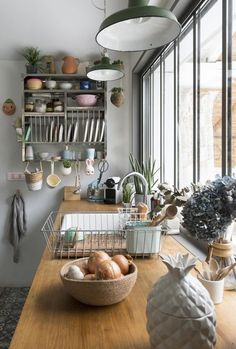 Love everything except the busy wall shelf. Would want more open shelving. Love the windows, counter, plants, light, feels