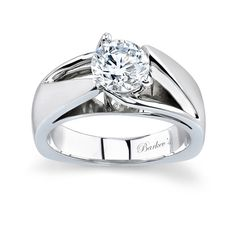 Dramatic, sure to catch the eye of many admirers this white gold solitaire engagement ring is artfully designed with a split shank and cathedral shoulders rising to the prong-set center diamond; a bright polished gallery adds to the contemporary feel. Also available in two-tone, all yellow gold, 18k and Platinum.