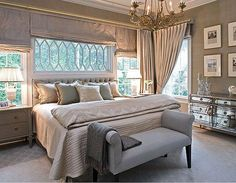 roman shades on wall to wall windows behind/beside bed