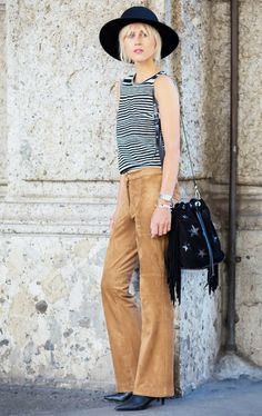 A striped tank top is worn with suede pants, boots, a felt hat, and fringe bucket bag
