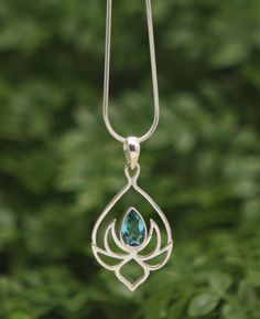 Teardrop pendant of sterling silver depicts a budding lotus flower and is inlaid with a glittering topaz gemstone. Hangs from an 18 inch chain.