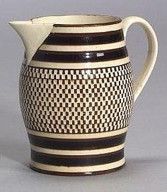 Checker Banded Mochaware Jug, England, c. 1790, rare red earthenware baluster-form jug banded with black and white slip, the broad white field diced in a fine checkerboard pattern on an engine-turning lathe the extruded white handle with foliate