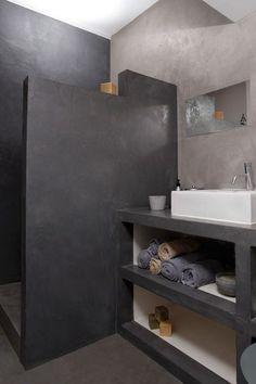 Cette salle de bains a été totalement rénovée à l'aide d'un béton ciré choisi en deux tons de gris pour créer un effet de profondeur et de contraste. Les murs, le sol, le mobilier, le bac et la paroi de la douche à l'italienne ont d'abord été enduits d'une sous-couche spécifique. Une fois le mortier appliqué, on a passé deux couches de bouche-pores translucide puis trois couches d'une finition haute résistance aspect satin. Un travail de fourmi pour un résultat bluffant ! Prix pour un…