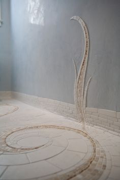 an exquisite hand-cut marble and limestone mosaic that unfurls up the subtly reflective, pale-blue Venetian plaster walls. #bathroom #tile #floor #swirl