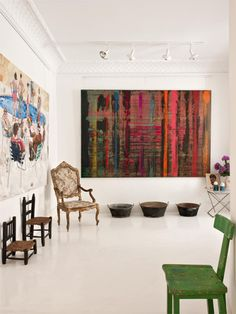 Art takes the forefront in this space.  That is why the furniture is minimal.  Don't have art like this in a room filled with small furniture as it will overwhelm...  But here, the art is balanced by all the white, empty space.