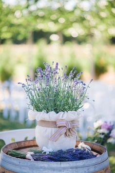 Wedding ceremony using live lavender plants as decor on wine barrel