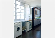 As tinas de aço foram fixadas com parafusos na parede da lavanderia. As alças servem para pendurar panos e até um pequeno vaso. Ainda sobre espaço para os divertidos cabideiros de alumínio, em forma de seta