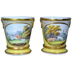 The yellow-ground cache pots and stands each have oval panels to front with a gilt band and an ornate gilt design of tulips above. Each panel is painted with bucolic scenes of cattle in landscapes. In one a windmill can be seen. Each rim with a wide gilt band and the moulded loop handles in gold too.