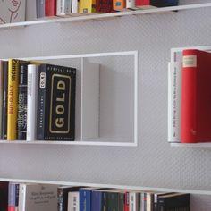 Durch die mimimale Materialverwendung entstehen stabile und filigrane Rahmen, welche die Bücher einfassen und wirkungsvoll präsentieren. Die unterschiedlich genormten Buchformate haben den Stahlrahmen ihre Maße verliehen. Die Konstruktion zur Wand ist nicht ersichtlich, da sie von den Büchern umschlossen wird, somit scheinen die Rahmen zu schweben. Durch die Anordung der Bücherrahmen, die unterschiedlichen Formate und Tiefen, entsteht ein lebendige, dreidimensionales Wandbild, das die…