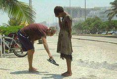 Man giving his shoes to a homless girl in Rio de Janeiro.