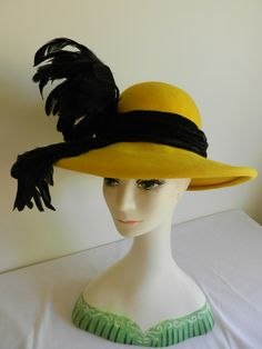 Black feather on Yellow felt hat by Raymond Hudd.