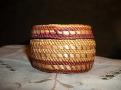 This is a tiny basket woven by the Makah Tribe of the Pacific Northwest Coast. It is 3 inches in diameter by 2 and a half inches high. It was made with Cedar strips, Cattail Leaves and sea grass. This one was made around 1920-1930