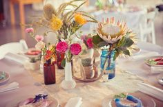 Love these centerpieces. Mixmatched vases, pops of bright colors...very mod and eclectic. Marfa Desert Magic Wedding: Emily + Colby