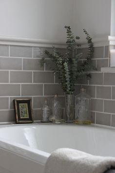 Bathroom : grey tiles, old bottles, eucalyptus branches.