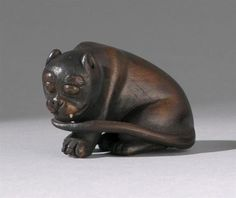 """WOOD NETSUKE 19th Century By Tomokazu. Depicting a seated tiger with inlaid eyes and teeth. Signed. Length 1.6"""" (4 cm)."""
