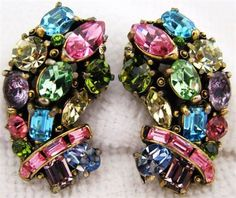 Vintage Hollycraft Copr 1955 jewelry earrings with multi colored rhinestones. Screw backs. Gold tone metal. These gorgeous earrings measure 1.25in. long by .75in. wide. Each earring has 18 rhinestones, in varying shades of blue, pink, green and purple. There are 6 different stone shapes, round, oval, baguette, marquise and emerald. The condition is good for their age, the purple oval stones in both earrings are showing some age to the foil backing. the rest are clean and sparkly.   Shipping…
