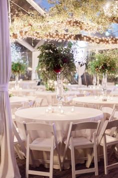 Wow! These tall, organic centerpieces and romantic candles were perfect for Rachel and Gabe's big day. The white decor and dazzling lights added to the timeless elegance. Captured by Stephanie Hunter Photography. // Rentals by Premiere Events. #bridesofaustin #wedding #tabletop #reception