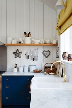 "[i]A white kitchen sink is inlaid into the counter. Jelly molds twinkle on the wall beneath a shelf used for white tableware. The marble worktop is paired with blue cabinets.[/i]  Like this? Then you'll love  [link url=""http://www.houseandgarden.co.uk/interiors/rustic-interior-design""]16 Rustic Interiors[/link]"