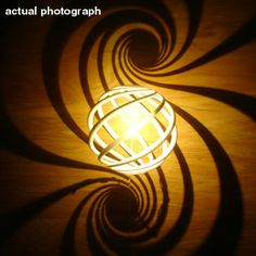 """Math Artwork"" -- Rather fabulous site with dozens and dozens of photos of art from ""tessellations, surfaces, and other math stuff."" Shown: ""Prototype sconce light"" -- this is an actual photograph, where much on the site is virtual."