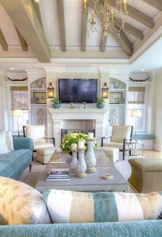 """Cottage Living Room with Chandelier, Distressed Ceramic Pillar Holders 9.5"""", Built-in bookshelf, Cement fireplace"""
