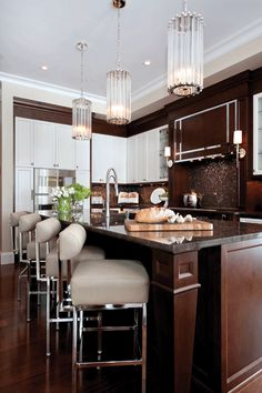 Shake up a classic colour scheme. White cabinets, dark island is a tried-and-true combination, but here it gets punched up a notch: rich brown gables frame each white cabinet, and iridescent Murano tiles add sparkle to the backsplash. #westernliving