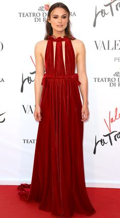 KEIRA KNIGHTLEY in a high-neck red gown with a tie waist, plus metallic sandals, at the La Traviata premiere in Rome.