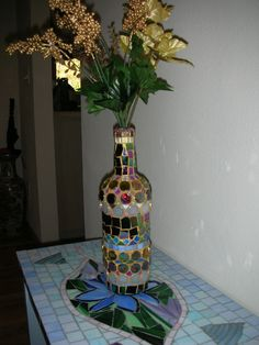Mosaic Wine Bottle Vase - You can cover an ordinary wine bottle with glass, beads, glitter tiles, and millefiori, and washed the grout with gold coloring to create a beautiful, one-of-a-kind decoration for your table.