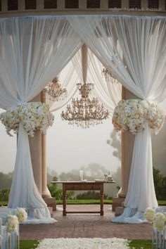 Drapery with outdoor ceremony pillars by whitney -no chandelier and smaller flower arrangement (for wedding reception with twinkle lights)