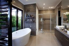 A modern, masculine style is created in this stunning bathroom with dark palette of chocolate and black. Contemporary pieces are used in the decor with tiled wallpaper giving the space a city feel.